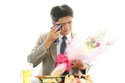 涙を拭く男性